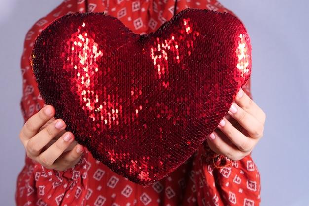 Vrouwen die rood hart in handen houden Premium Foto