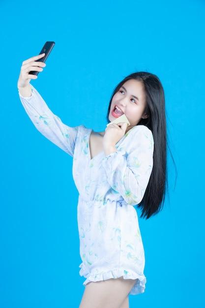 Vrouwen die smartcards en mobiele telefoons grijs houden Gratis Foto