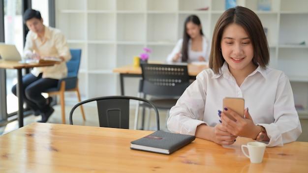 Vrouwen die smartphone gebruiken in het café ze zitten op een sociale afstand. Premium Foto