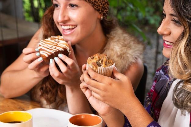 Vrouwen die snoepjes eten bij koffiewinkel Gratis Foto