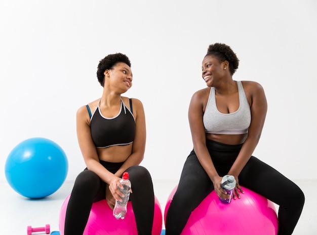 Vrouwen doen oefeningen op fitness bal Gratis Foto