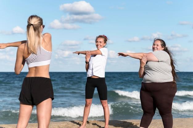 Vrouwen doen oefeningen op het strand Gratis Foto