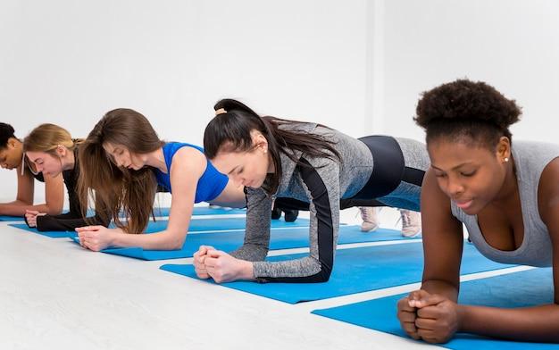 Vrouwen doen resitance oefening op mat Gratis Foto