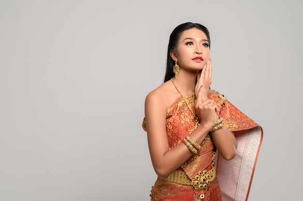 Vrouwen dragen thaise kleding en handen raken hun gezicht aan Gratis Foto