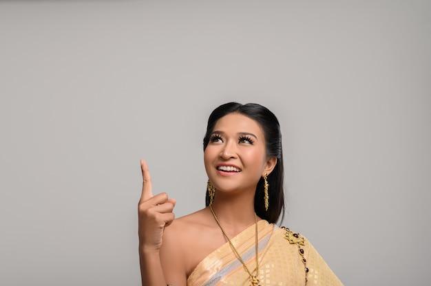 Vrouwen dragen thaise kostuums die symbolisch zijn, wijzende vingers Gratis Foto