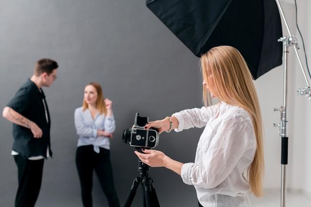 Vrouwen en man die in een fotografiestudio werken Gratis Foto