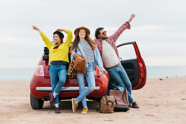 Vrouwen en man met upped handen in de buurt van de auto op het strand Gratis Foto