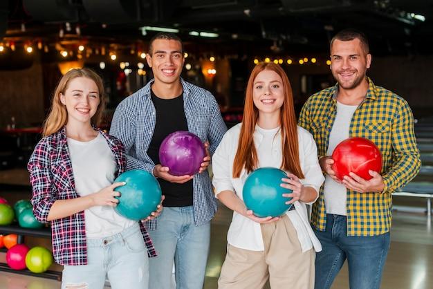Vrouwen en mannen die het kleurrijke middelgrote schot van kegelenballen houden Gratis Foto