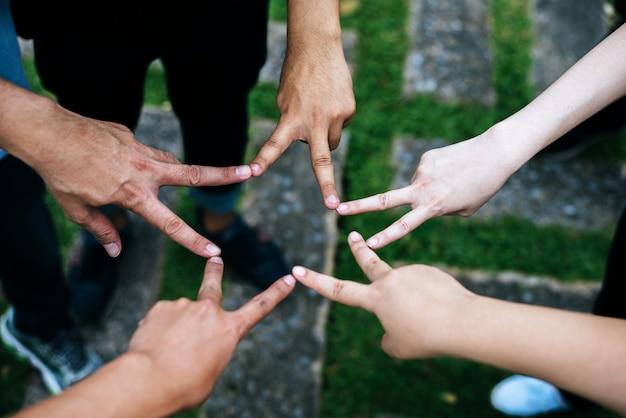Vrouwen en mannen vrienden maken stervorm van vingers. succes, vriendschapsconcept. Gratis Foto