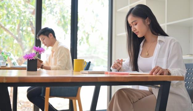 Vrouwen en mannen werken in het café, ze zitten op een sociale afstand. Premium Foto