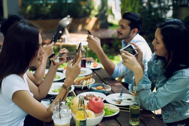 Vrouwen en vrienden gebruiken een telefoon tussen de maaltijden door Premium Foto
