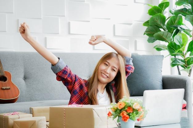 Vrouwen glimlachen gezicht met opgeheven arm met de doos met haar te leveren producten Premium Foto
