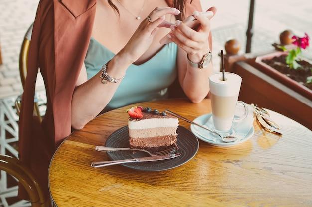 Vrouwen handen met telefoon en schrijft een bericht in een café Premium Foto