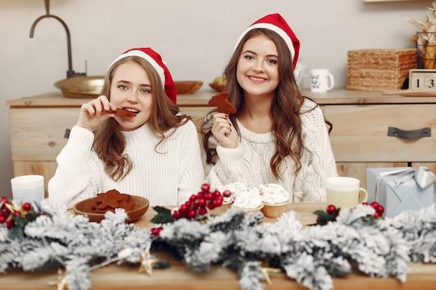 Vrouwen hebben cupcakes. vrienden in kerstversieringen. meisje in een kerstmuts. Gratis Foto