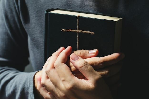 Vrouwen houden de bijbel en kruisen van zegen van god. vrouwen in religieuze concepten Premium Foto