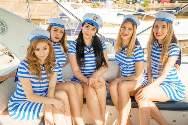Vrouwen in gestreepte jurken en petten, op het dek van een jacht, Premium Foto