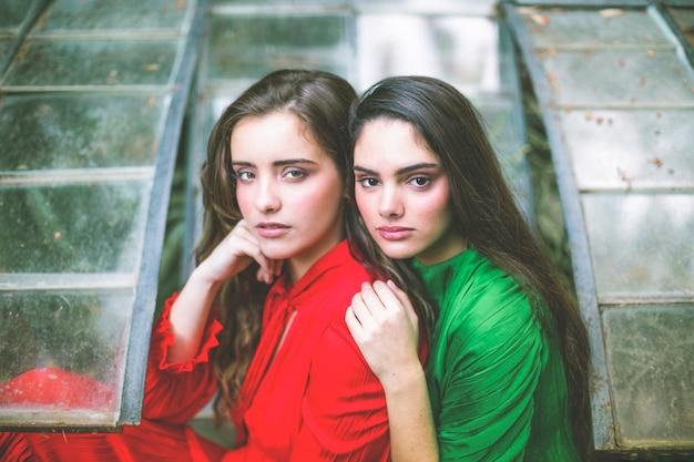 Vrouwen in rode en groene jurken kijken naar de camera Gratis Foto