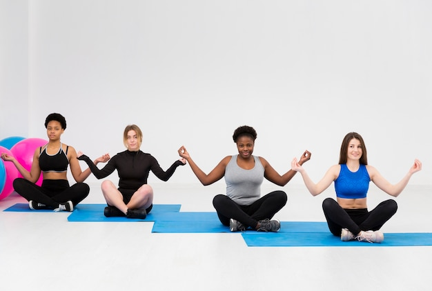 Vrouwen in yogapositie bij fitnessles Gratis Foto