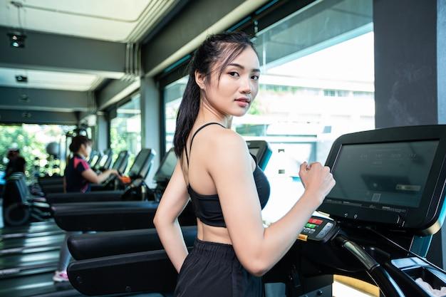 Vrouwen joggen op de loopband in de sportschool Gratis Foto