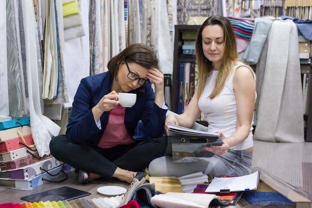 Vrouwen kijken monsters van stoffen voor gordijnen, meubels Premium Foto