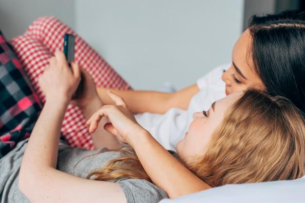 Vrouwen knuffelen in bed en hebben plezier in de telefoon Gratis Foto