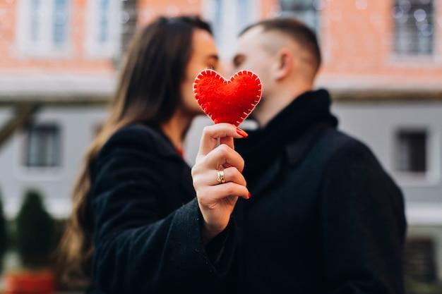 Vrouwen kussende man terwijl het tonen van rood hart Gratis Foto