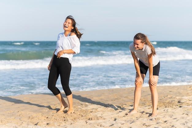 Vrouwen lachen op het strand tijdens het joggen Gratis Foto