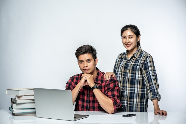 Vrouwen leren mannen op het werk met laptops te werken. Gratis Foto