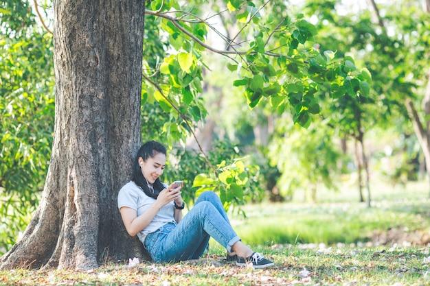 Vrouwen luisteren naar muziek en ontspannen onder de bomen. Premium Foto