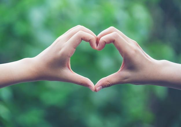 Vrouwen maken hartvormen met hun handen Premium Foto