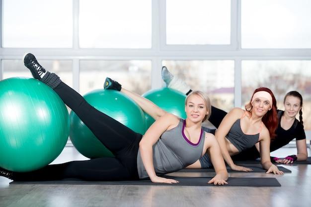 Vrouwen met een been over een bal Gratis Foto