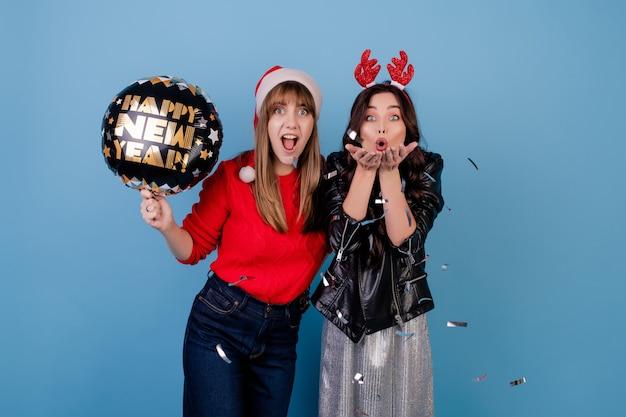 Vrouwen met gelukkige nieuwe jaarballon die zilveren confettien blazen die kerstmishoed dragen die over blauw wordt geïsoleerd Premium Foto