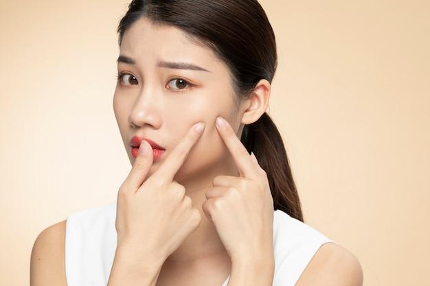 Vrouwen met gezichtshuidproblemen - ongelukkige jonge vrouwen die haar huid op een oranje achtergrond raken Premium Foto
