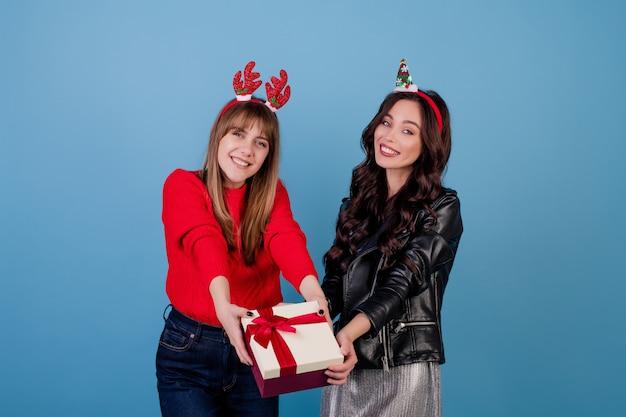 Vrouwen met giftdoos met lint die grappige die kerstmishoepels dragen over blauw worden geïsoleerd Premium Foto