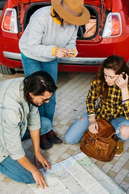Vrouwen met rugzak en smartphone dichtbij de mens die kaart dichtbij auto bekijken Gratis Foto