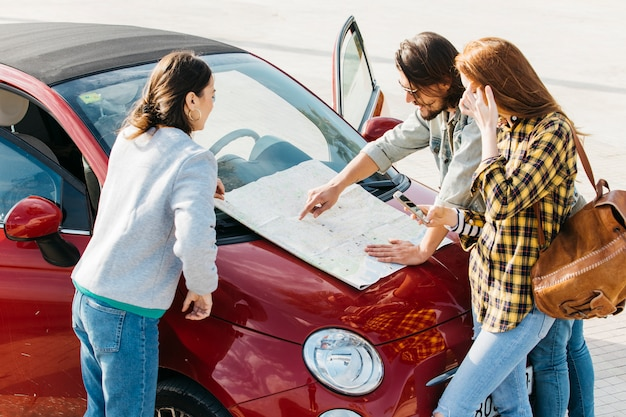 Vrouwen met rugzak en smartphone dichtbij de mens die kaart op autokap bekijken Gratis Foto