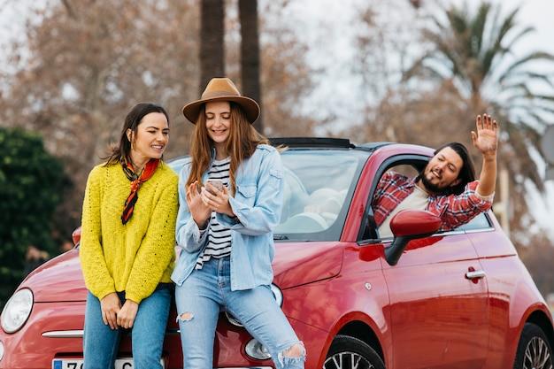 Vrouwen met smartphone dichtbij de mens die uit auto leunen Gratis Foto