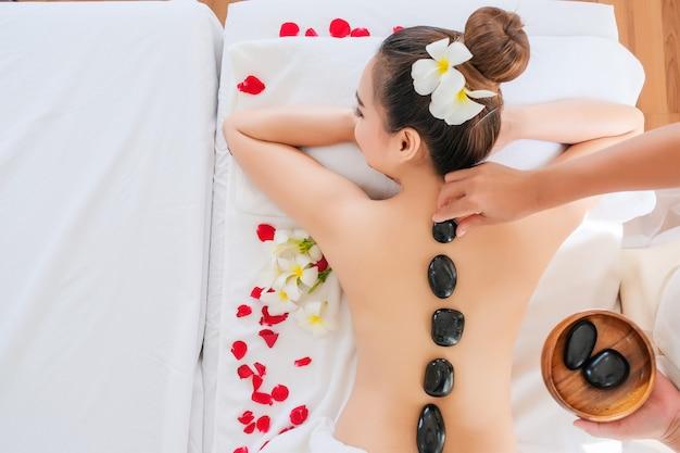 Vrouwen met therapeutische stenen op haar rug Premium Foto