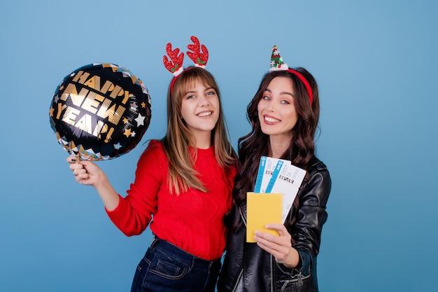 Vrouwen met vliegtuigkaartjes en gelukkige nieuwe die jaarballon over blauw wordt geïsoleerd Premium Foto