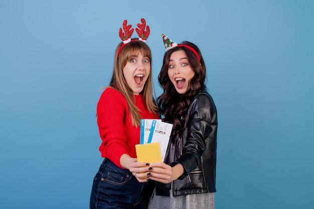 Vrouwen met vliegtuigtickets en paspoort die grappige die kerstmishoepels dragen over blauw worden geïsoleerd Premium Foto