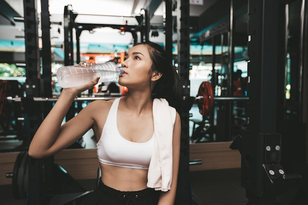 Vrouwen na het sporten drinken water uit flessen en zakdoeken in de sportschool. Gratis Foto