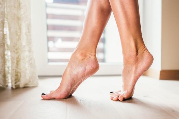 Vrouwen naakte voeten die op de vloer van het lighrparket dichtbij groot venster, close-up lopen. Premium Foto