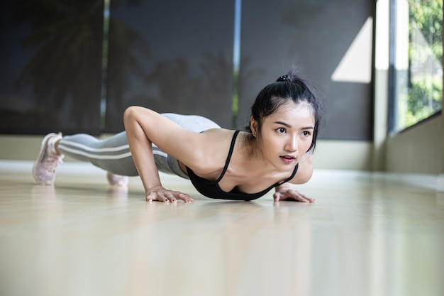 Vrouwen oefenen door de vloer in de sportschool te duwen Gratis Foto