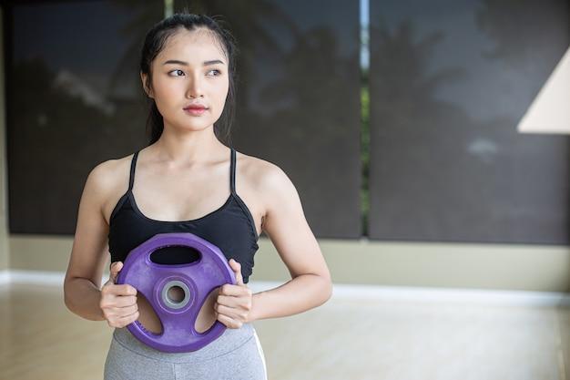 Vrouwen oefenen met haltergewichtplaten in de borst. Gratis Foto