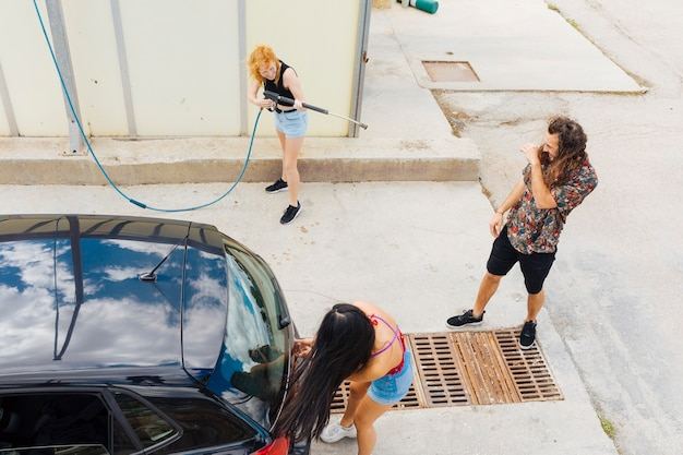 Vrouwen opspattend water op vrienden bij autowasserette Gratis Foto