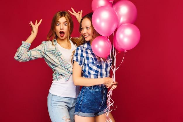 Vrouwen poseren met grote geschenkdoos en roze ballonnen Gratis Foto