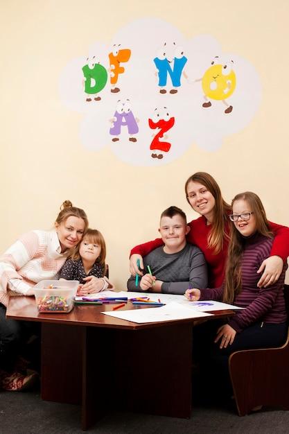 Vrouwen poseren met kinderen met het syndroom van down Gratis Foto