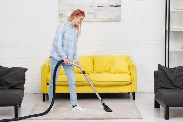 Vrouwen schoonmakend tapijt met vacuüm Gratis Foto
