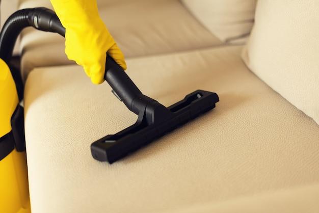 Vrouwen schoonmakende bank met gele stofzuiger. ruimte kopiëren. schoon concept Premium Foto