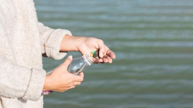 Vrouwen schoonmakende overzees van plastic fles Gratis Foto